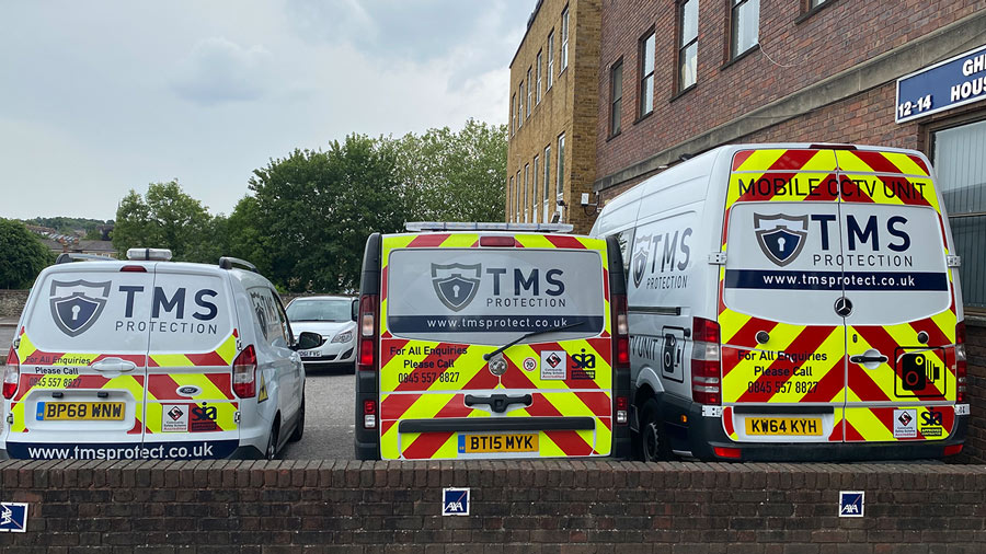 Three parked TMS Vans